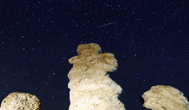 A meteor streaks past stars in the night sky