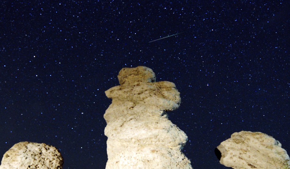 A meteor streaks past stars in the night sky
