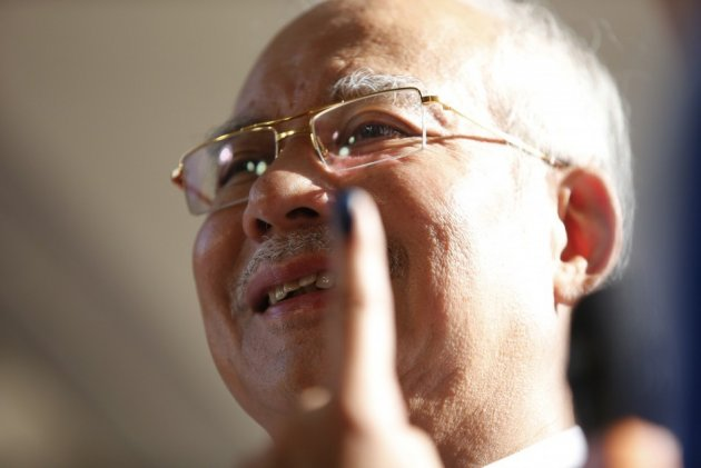 Malaysia's Prime Minister Najib Razak shows his finger with the 'indelible' ink to the media after casting his vote during the general elections