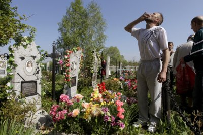 A man drinks vodka at a grave during Orthodox Easter in the village of Pogost, some 250 km 155 miles south of Minsk May 5, 2013. Villagers in southern parts of Belarus visit their relatives graves during Easter celebrations on Sunday.