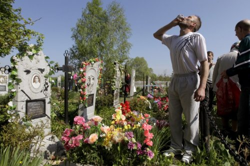 A man drinks vodka at a grave during Orthodox Easter in the village of Pogost, some 250 km (155 miles) south of Minsk May 5, 2013. Villagers in southern parts of Belarus visit their relatives' graves during Easter celebrations on Sunday.