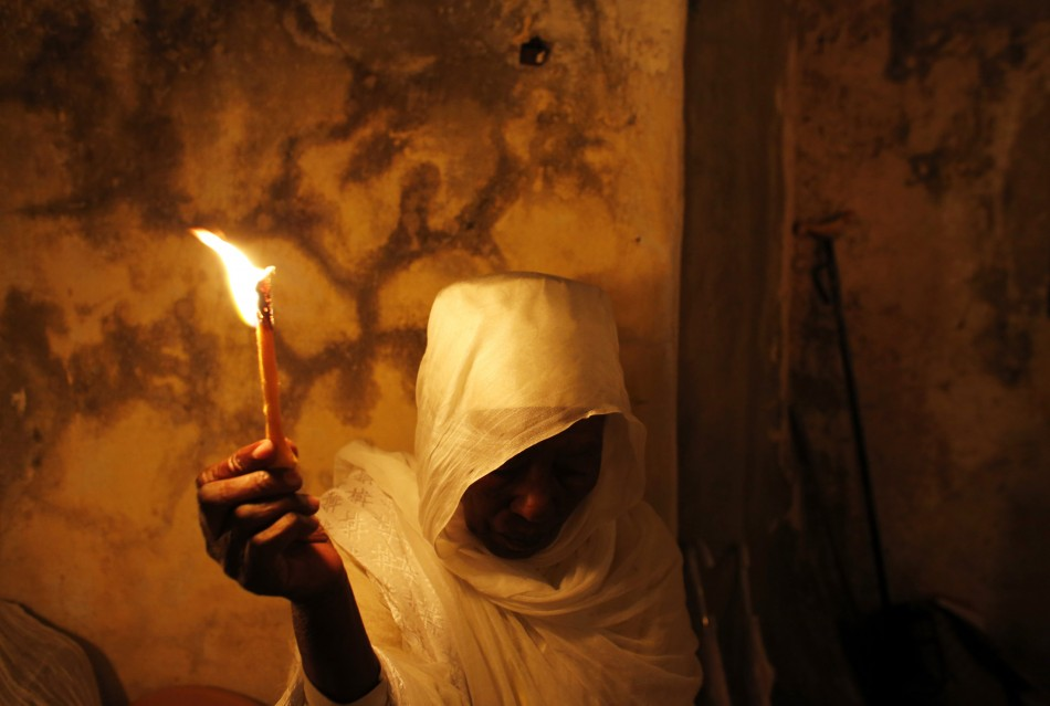 An Ethiopian Orthodox worshipper holds a candle during the Holy Fire ceremony at the Ethiopian section of the Church of the Holy Sepulchre in Jerusalems Old City May 4, 2013.