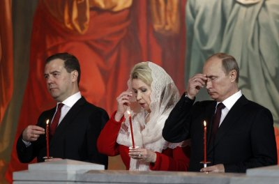 Russian President Vladimir Putin R, Prime Minister Dmitry Medvedev L and his wife Svetlana C attend an Orthodox Easter service conducted by the Patriarch of Moscow and All Russia Kirill in the Christ the Saviour Cathedral in Moscow May 5, 2013.