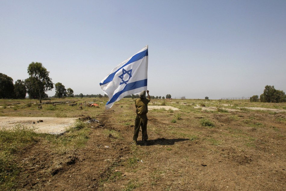 An Israeli soldier places a flag close to the ceasefire line between Israel and Syria