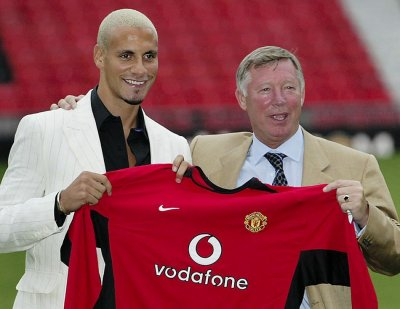 July 22 2002 Uniteds new signing Rio Ferdinand holds up his shirt with Ferguson at Old Trafford. United signed the centre-back for a then-British record of 30 million 47.27 million from Leeds United.