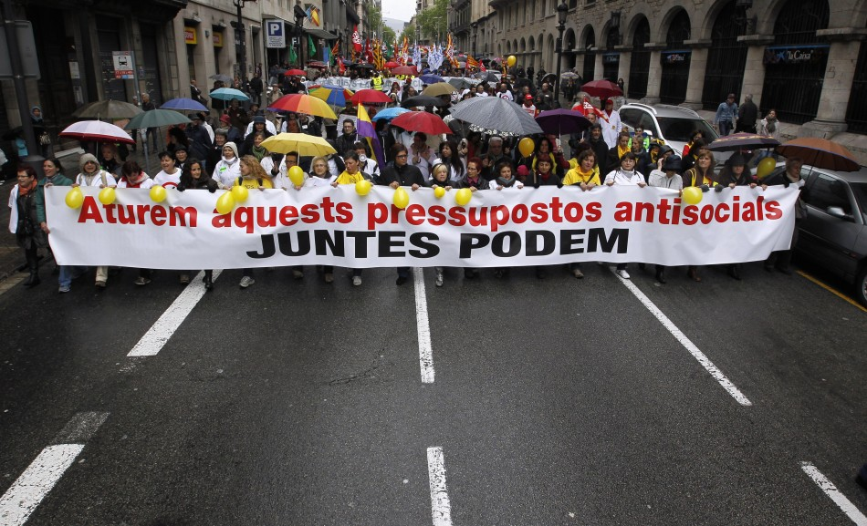People hold banners as they march during a protest against government austerity measures in Barcelona April 28, 2013. The banner reads