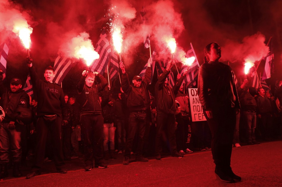 Supporters of the extreme-right Golden Dawn party hold flares as they chant the national anthem, during a rally over the crisis in Cyprus, outside the German embassy in Athens March 22, 2013. Cyprus was just hours away from a deal on Friday to raise billi