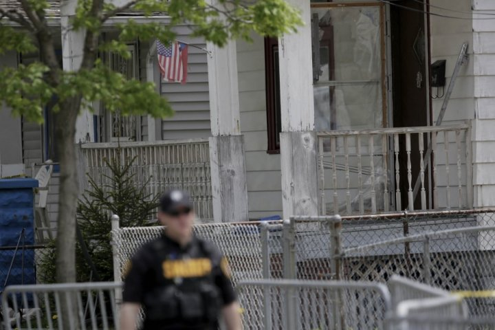 A police officer walks past the house where the three woman were held for a decade (Reuters)