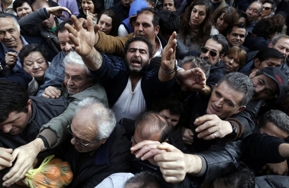 People reach out to take fruits and vegetables freely distributed by farmers during a protest against high production costs outside the Agriculture Ministry in Athens February 6, 2013 (Photo: Reuters)