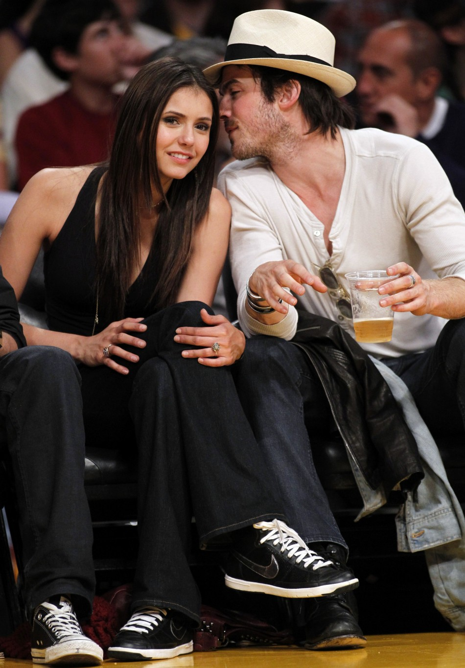 Canadian actress Nina Dobrev (L) sits court side with actor Ian Somerhalder