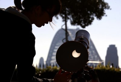 A woman adjusts a telescope showing on a screen the annular solar eclipse from atop Observatory Hill in Sydney May 10, 2013.