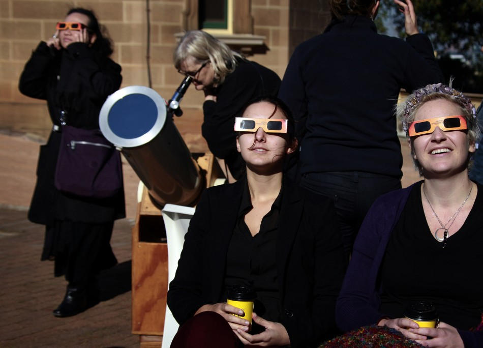 Women wearing protective glasses sit near another woman looking through a telescope at the annular solar eclipse from atop Observatory Hill in Sydney May 10, 2013.