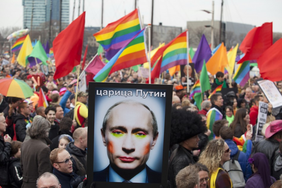 A demonstrator holds up a picture depicting Russian President Vladimir Putin with make-up,