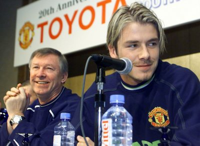 David Beckham speaking to reporters with Manchester Uniteds head coach Alex Ferguson during a news conference following their arrival in Tokyo November 27 1999.