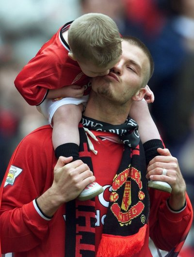 David Beckham gets a kiss from his son Brooklyn after winning the premiership at Old Trafford in Manchester, May 5, 2001.