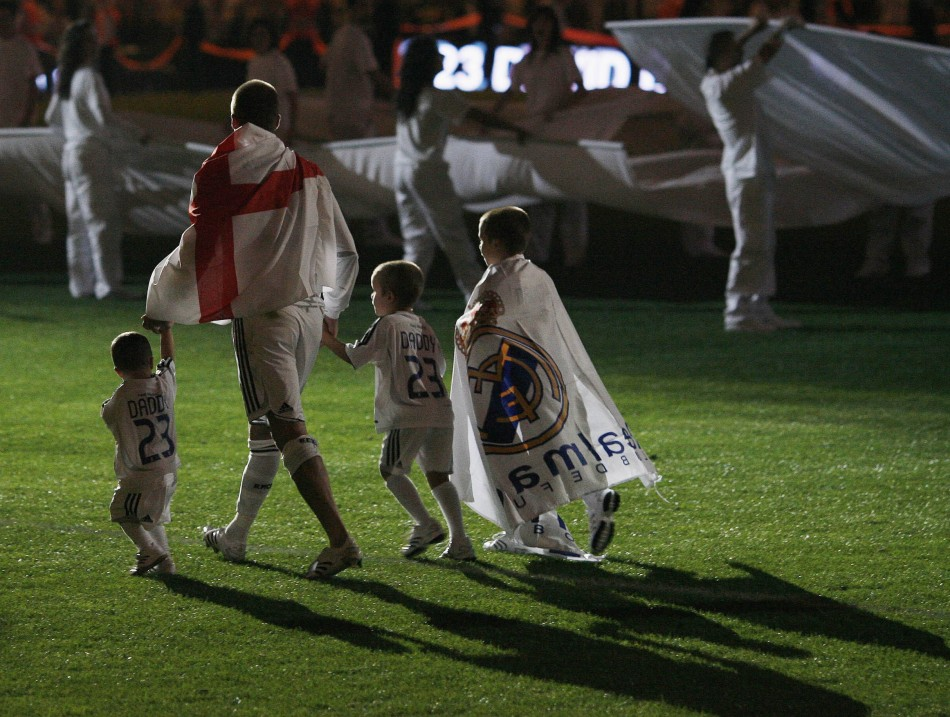 David Beckham walks away with his sons, Cruz L, Romeo and Brooklyn R, after their Spanish First Division soccer match victory over Real Mallorca at the Santiago Bernabeu stadium in Madrid June 17, 2007.