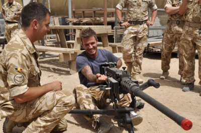 David Beckham C is seen cocking a Heavy Machine Gun during a visit to Camp Bastion, in Afghanistan in this May 22, 2010 handout photograph.
