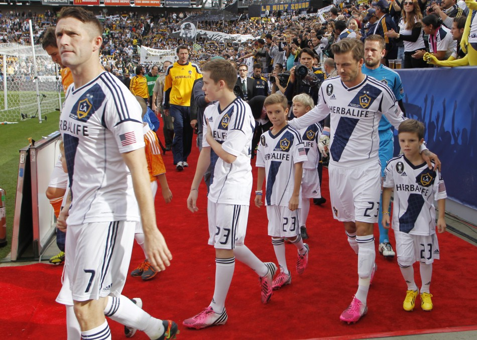 David Beckham walks out to the field with his sons Brooklyn 2nd L, Romeo 3rd R and Cruz R along with teammates including Robbie Keane L of Ireland before the MLS Cup championship soccer game against Houston Dynamo in Carson, California, December 1
