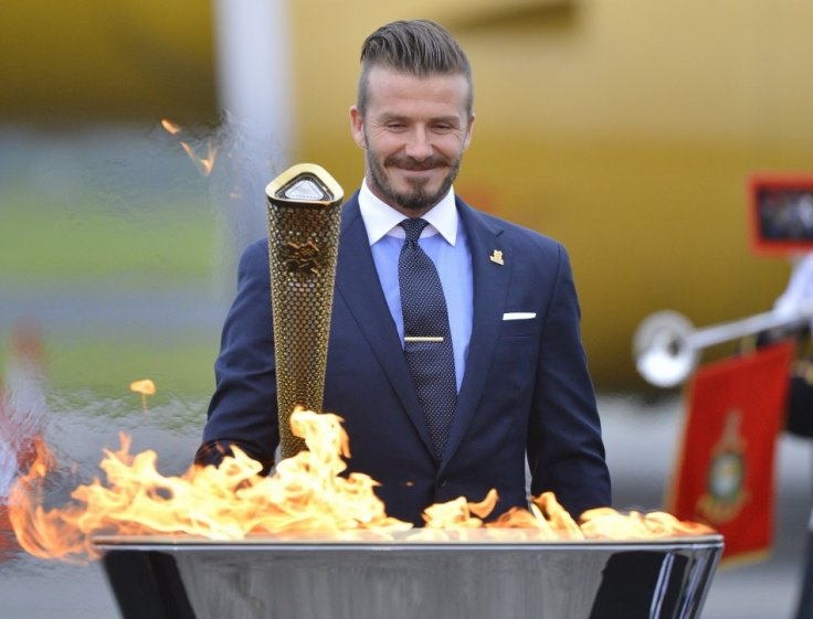 Soccer player and London 2012 Olympic Games ambassador David Beckham reacts after lighting the Olympic torch with a cauldron after arriving at RNAS Culdrose base near Helston in Cornwall, south west England May 18, 2012.