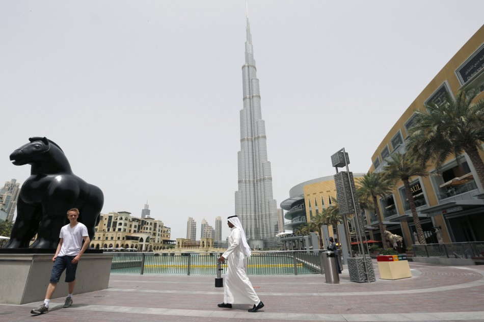 An Emirati man walks past a tourist posing for a photo near the Burj Khalifa, the tallest tower in the world, in Dubai May 9, 2013. (Photo: REUTERS)