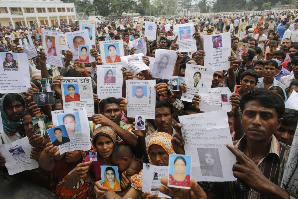 Relatives mourn as they show pictures of garment workers, who are believed to be trapped under the rubble of the collapsed Rana Plaza building, in Savar, 30 km (19 miles) outside Dhaka April 28, 2013. (Photo: Reuters)
