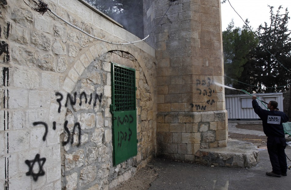 """A labourer cleans graffiti off a vandalised mosque in Jerusalem December 14, 2011. The graffiti to the left reads in Hebrew """"Mohammed is a pig."""""""