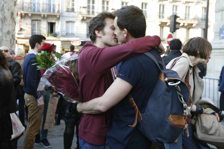 A gay couple kiss as people gather to celebrate after the French parliament approved a law allowing same-sex couples to marry and to adopt children,