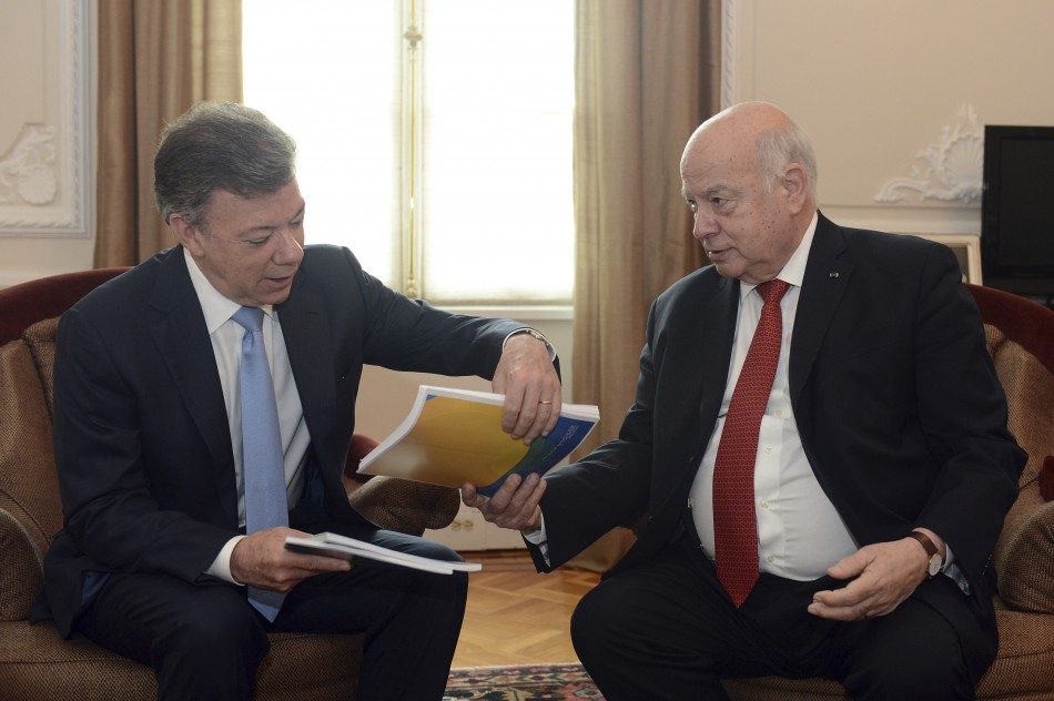 Colombia's President Juan Manuel Santos (L) receives a document from Jose Miguel Insulza, General Secretary of the Organization for the American States (OAS), during a meeting at presidential palace in Bogota May 17, 2013. Insulza Santos presented a report analyzing the fight against drugs trafficking in America.