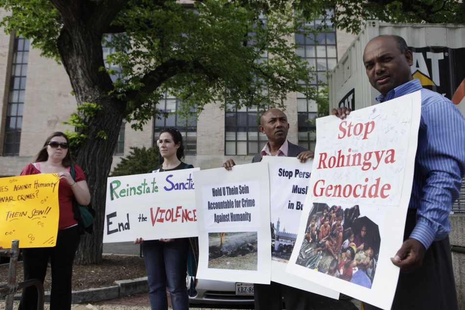 Protesters rally outside the Voice of America headquarters building before the arrival of Myanmar President Thein Sein