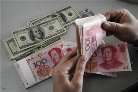 An employee counts Renminbi banknotes at a Bank of China branch in Changzhi, Shanxi province Nov. 16, 2009.