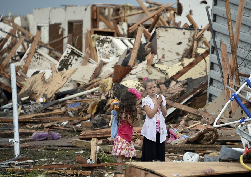 Two girls stand in rubble after a tornado struck Moore, Oklahoma, May 20, 2013. A 2-mile-wide (3-km-wide) tornado tore through the Oklahoma City suburb of Moore on Monday, killing at least 51 people while destroying entire tracts of homes, piling cars atop one another, and trapping two dozen school children beneath rubble.