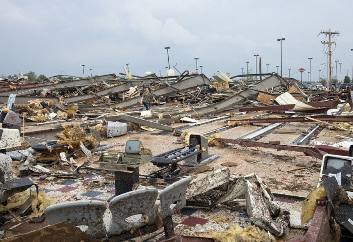 A woman walks through debris after a huge tornado struck Moore, Oklahoma (Reuters)