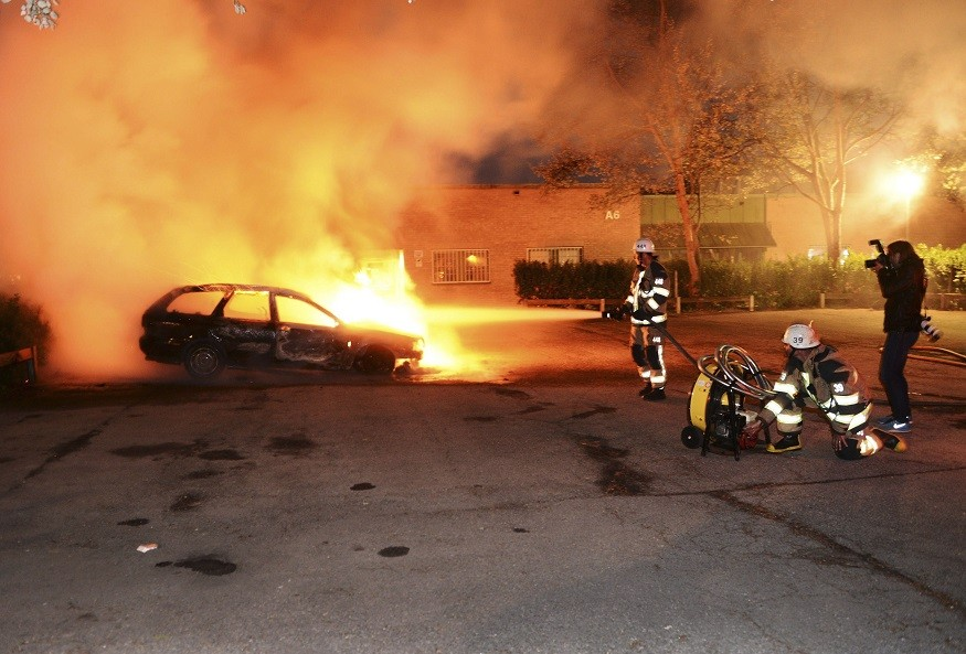 Firefighters extinguish a burning car, following riots in the Stockholm suburb of Kista (Reuters)