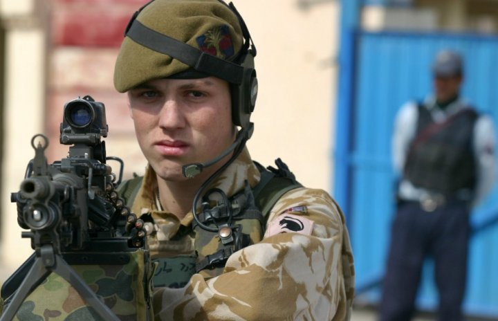 Young British soldier with Afghan officer behind him