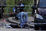 A police forensics officer investigates a crime scene where one man was killed in Woolwich, southeast London(Reuters)