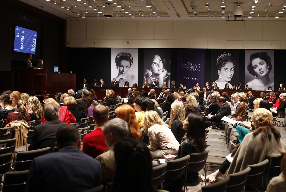 People sit near images of Elizabeth Taylor during an auction of the late actress jewelry, clothing, art and memorabilia at Christies auction house