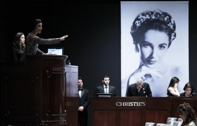 Christies auctioneer Andrea Fiuczynski conducts an auction of Elizabeth Taylors jewellery, clothing, art and memorabilia, near an image of the late actress at Christies auction house in New York, December 14, 2011