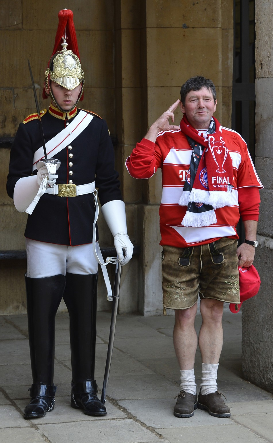 A Bayern Munich supporter poses next to a member of The Queen's Life Guard standing on duty outside of Horse Guards in central London