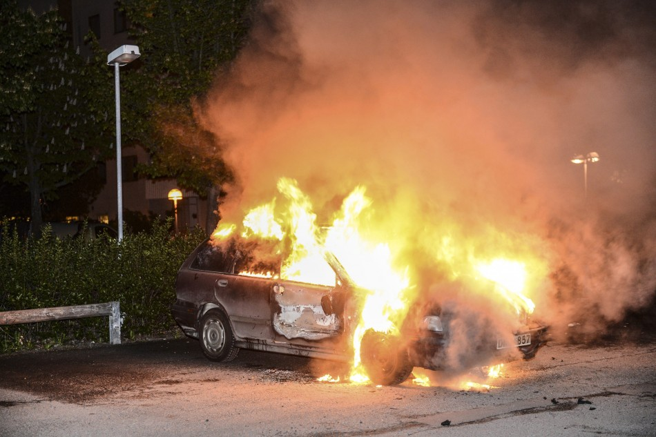 A car set on fire burns, following riots in the Stockholm suburb of Kista