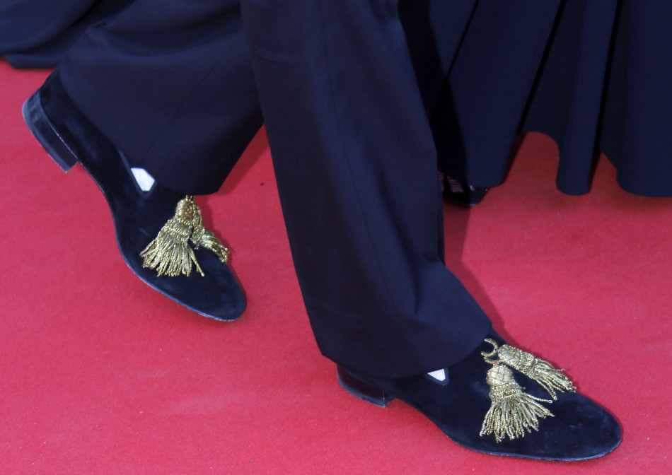 The shoes of French designer Christian Louboutin are pictured as he poses on the red carpet for the screening of the film Le Passe The Past in competition during the 66th Cannes Film Festival in Cannes May 17, 2013.