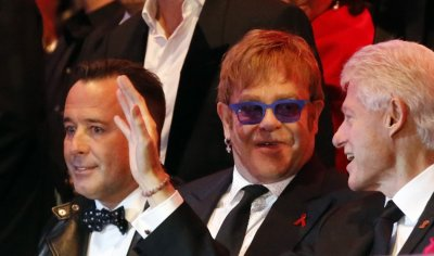 British singer Elton John C and his partner David Furnish L listen to former U.S. President Bill Clinton R during the opening ceremony of the 21st Life Ball in Vienna