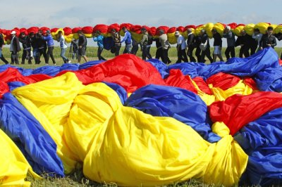 Workers carry Romanias national flag during a Guinness World Record attempt for the worlds biggest national flag in Clinceni, near Bucharest May 27, 2013.