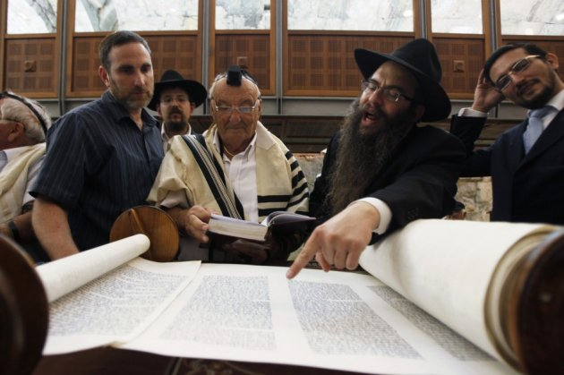 Holocaust survivor Israel Levin (3rd R) reads from a Torah scroll during his Bar Mitzvah ceremony at the Western Wall