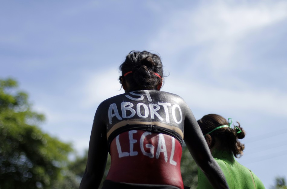 """A woman sits in a float with """"Yes abortion legal"""" written on her back during a protest in San Salvado"""