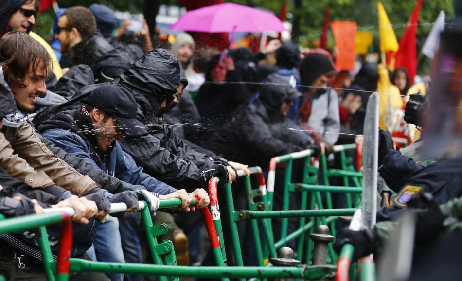 Riot police use pepper spray to prevent protestors from breaking through barricades near the European Central Bank