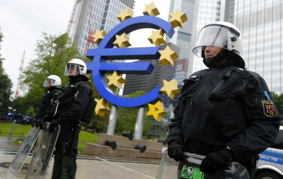 Riot police stand near the euro sign in front of the European Central Bank