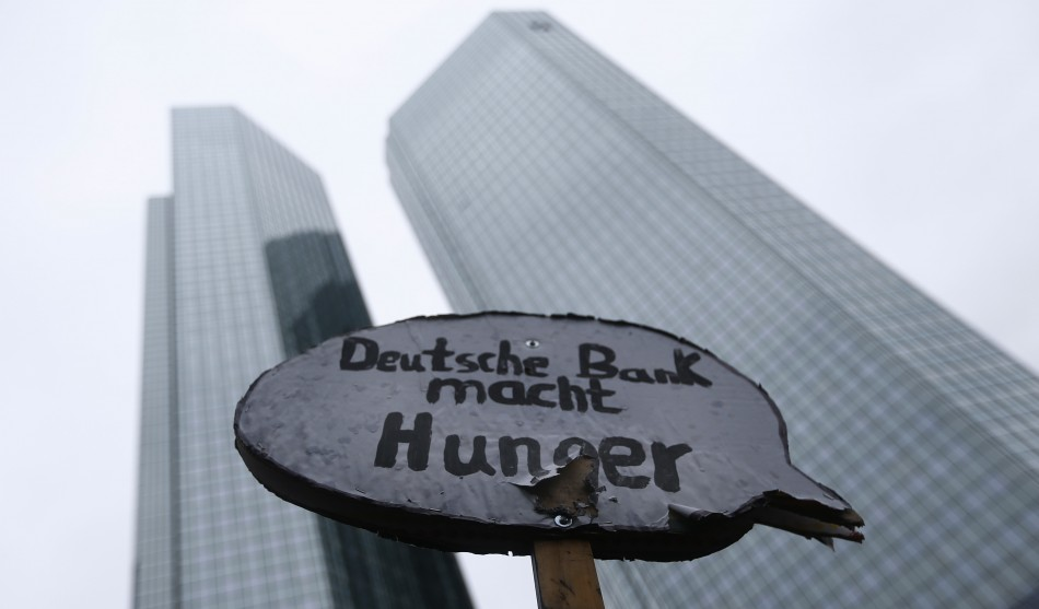 A protester holds a placard reading Deutsche Bank causes hunger in front of the headquarters of Germanys largest business bank, Deutsche Bank