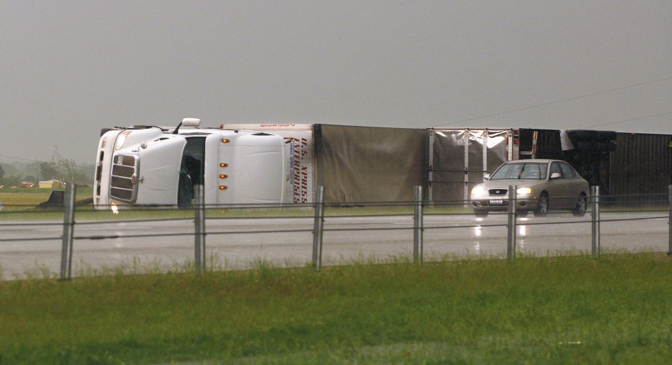 A car passes two semi tractor-trailers, flipped by a tornado, along Interstate-40 eastbound