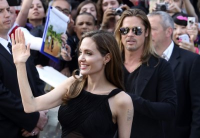 Angelina Jolie poses with her partner  Brad Pitt as they arrive for the world premiere of his film World War Z in London June 2, 2013.