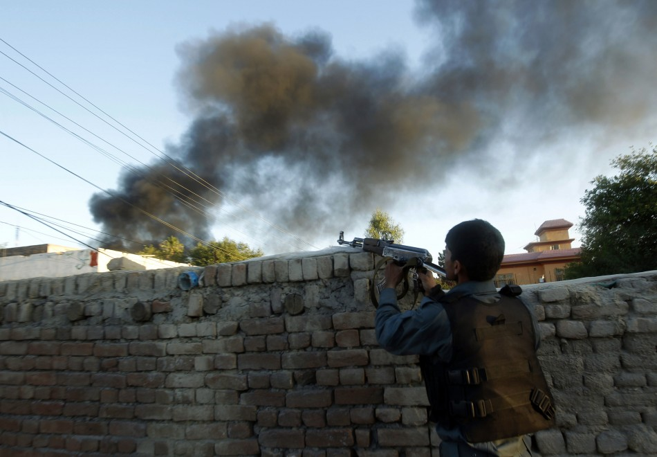An Afghan policeman takes up position as smoke billows from the site of the ICRC compound